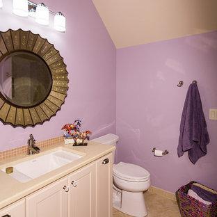 Idee per una stanza da bagno tradizionale di medie dimensioni con ante in stile shaker, ante bianche, WC a due pezzi, piastrelle beige, pareti viola, pavimento in pietra calcarea, lavabo sottopiano e top in superficie solida