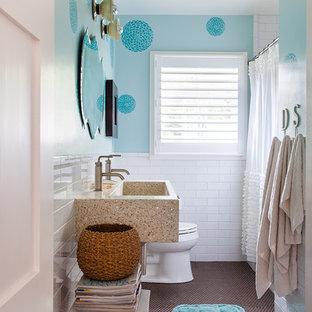 Diseño de cuarto de baño infantil, contemporáneo, de tamaño medio, con lavabo de seno grande, encimera de cemento, bañera empotrada, sanitario de una pieza, baldosas y/o azulejos blancos, baldosas y/o azulejos de cerámica, paredes azules, suelo con mosaicos de baldosas y ducha con cortina