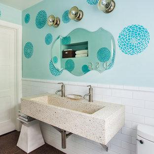 Cette image montre une salle de bain design de taille moyenne pour enfant avec une grande vasque, un plan de toilette en béton, une baignoire en alcôve, un WC à poser, un carrelage blanc, des carreaux de céramique, un mur bleu et un sol en carrelage de terre cuite.