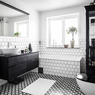 Inredning av ett skandinaviskt stort svart svart en-suite badrum, med en öppen dusch, en vägghängd toalettstol, vit kakel, keramikplattor, vita väggar, cementgolv, granitbänkskiva, flerfärgat golv, med dusch som är öppen, släta luckor, svarta skåp, ett hörnbadkar och ett fristående handfat