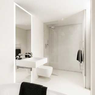 This is an example of a large modern family bathroom in London with a freestanding bath, a wall mounted toilet, beige tiles, white tiles, beige walls, ceramic flooring, a wall-mounted sink, an open shower, a built-in shower and white floors.