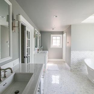 Esempio di un'ampia stanza da bagno padronale tradizionale con ante di vetro, ante bianche, vasca freestanding, doccia doppia, WC monopezzo, pareti grigie, pavimento in marmo, lavabo sottopiano e top in quarzite
