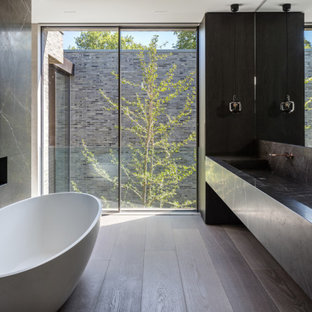Modern bathroom in London with a freestanding bath, dark hardwood flooring, a trough sink, brown floors, grey worktops, a wall niche, double sinks and a floating vanity unit.