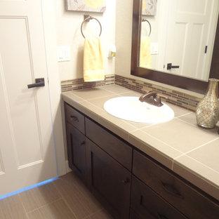 Immagine di una stanza da bagno con doccia classica di medie dimensioni con ante in stile shaker, ante in legno bruno, piastrelle beige, piastrelle a listelli, pareti beige, pavimento in gres porcellanato, lavabo da incasso e top piastrellato