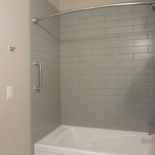 Esempio di una stanza da bagno con doccia chic di medie dimensioni con ante lisce, ante in legno scuro, vasca ad alcova, vasca/doccia, piastrelle grigie, piastrelle in ceramica, pareti beige, pavimento con piastrelle in ceramica, lavabo sottopiano e top piastrellato