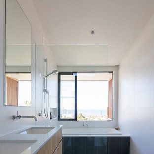 Contemporary 3/4 bathroom in Sydney with flat-panel cabinets, light wood cabinets, a drop-in tub, a curbless shower, gray tile, white walls, an undermount sink, grey floor, an open shower and white benchtops.