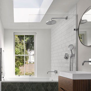 Design ideas for a contemporary bathroom in London with flat-panel cabinets, dark wood cabinets, a drop-in tub, a curbless shower, white tile, subway tile, white walls, a console sink, grey floor and an open shower.