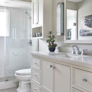 Inspiration för mellanstora klassiska badrum, med beige skåp, en dusch i en alkov, en toalettstol med separat cisternkåpa, vit kakel, keramikplattor, beige väggar, klinkergolv i keramik, ett undermonterad handfat, bänkskiva i kvarts, beiget golv, dusch med gångjärnsdörr och luckor med infälld panel