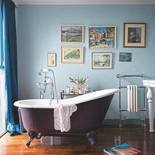 Exempel på ett mellanstort klassiskt badrum, med ett badkar med tassar, blå väggar och mörkt trägolv