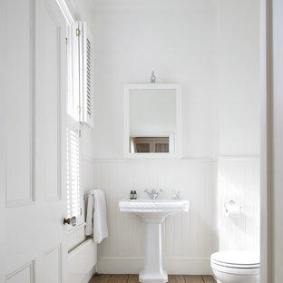 This is an example of a victorian bathroom in Sussex with a pedestal sink, white walls, medium hardwood floors and brown floor.