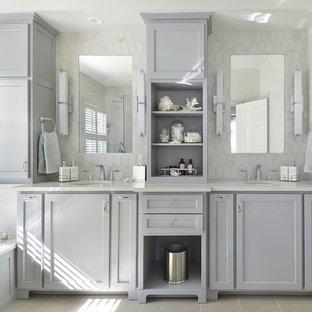 Idéer för att renovera ett mellanstort vintage en-suite badrum, med ett undermonterad handfat, luckor med infälld panel, grå skåp, bänkskiva i kvarts, ett platsbyggt badkar, vit kakel, porslinskakel, vita väggar och klinkergolv i porslin