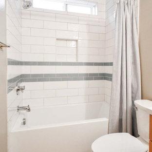 Foto på ett litet funkis vit badrum med dusch, med släta luckor, skåp i ljust trä, en dusch/badkar-kombination, en toalettstol med separat cisternkåpa, vit kakel, tunnelbanekakel, beige väggar, korkgolv, ett undermonterad handfat, bänkskiva i kvarts, rött golv och dusch med duschdraperi