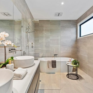 Modern wet room bathroom in Melbourne with flat-panel cabinets, dark wood cabinets, a freestanding tub, beige tile, a vessel sink, beige floor, an open shower and white benchtops.