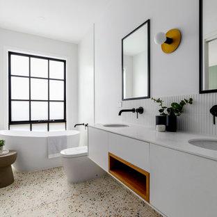 Свежая идея для дизайна: главная ванная комната в современном стиле с плоскими фасадами, белыми фасадами, отдельно стоящей ванной, белой плиткой, белыми стенами, полом из терраццо, врезной раковиной, разноцветным полом, белой столешницей, тумбой под две раковины и подвесной тумбой - отличное фото интерьера