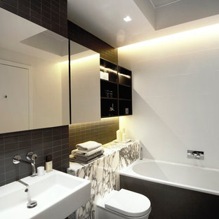 Inspiration for a large contemporary master bathroom in London with a wall-mount sink, marble benchtops, a drop-in tub, a wall-mount toilet, porcelain tile and porcelain floors.
