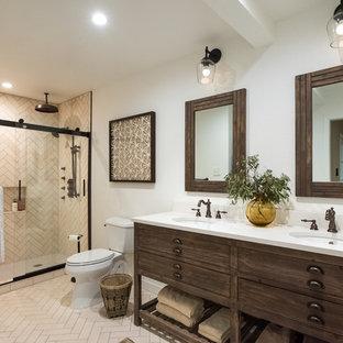 オースティンの中サイズのトランジショナルスタイルのおしゃれなマスターバスルーム (白いタイル、ライムストーンの床、珪岩の洗面台、白い洗面カウンター、家具調キャビネット、濃色木目調キャビネット、アルコーブ型シャワー、分離型トイレ、白い壁、ベージュの床、引戸のシャワー) の写真