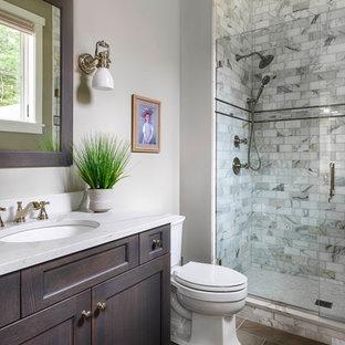 Klassisches Badezimmer mit Schrankfronten mit vertiefter Füllung, dunklen Holzschränken, Duschnische, grauen Fliesen, weißer Wandfarbe, Unterbauwaschbecken, braunem Boden, Falttür-Duschabtrennung, weißer Waschtischplatte und Einzelwaschbecken in Boston