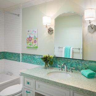 Modelo de cuarto de baño infantil, clásico renovado, con lavabo bajoencimera, armarios con rebordes decorativos, puertas de armario blancas, encimera de vidrio reciclado, baldosas y/o azulejos verdes, baldosas y/o azulejos de cerámica, paredes verdes y suelo de baldosas de porcelana