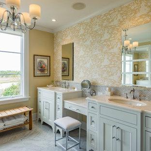 Réalisation d'une salle de bain principale tradition avec un placard avec porte à panneau encastré, des portes de placard blanches, un mur jaune et un lavabo encastré.