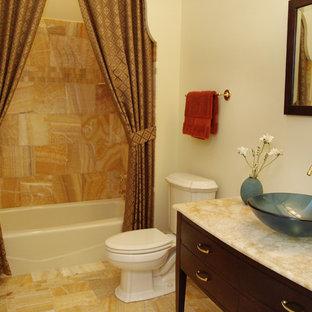 Modelo de cuarto de baño clásico, de tamaño medio, con armarios con paneles lisos, puertas de armario de madera en tonos medios, bañera empotrada, combinación de ducha y bañera, sanitario de dos piezas, lavabo sobreencimera, encimera de ónix, baldosas y/o azulejos multicolor, baldosas y/o azulejos de mármol, paredes amarillas y suelo de mármol