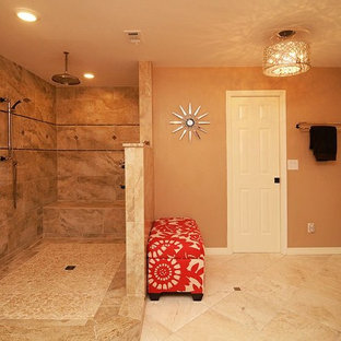 Corner shower - large traditional master beige tile and stone tile travertine floor corner shower idea in Tampa with an undermount sink, recessed-panel cabinets, dark wood cabinets, granite countertops, a two-piece toilet and orange walls