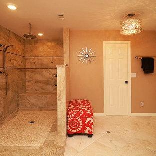タンパの大きいトラディショナルスタイルのおしゃれなマスターバスルーム (アンダーカウンター洗面器、落し込みパネル扉のキャビネット、濃色木目調キャビネット、御影石の洗面台、コーナー設置型シャワー、分離型トイレ、ベージュのタイル、石タイル、オレンジの壁、トラバーチンの床) の写真