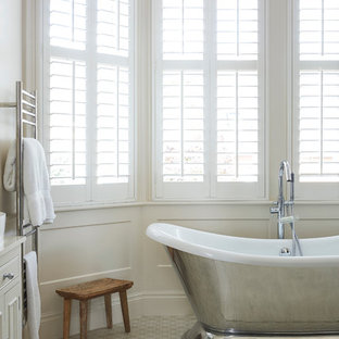 Photo of a traditional bathroom in London with beige cabinets, a freestanding bath, white tiles, mosaic tiles, white walls and mosaic tile flooring.