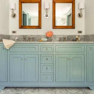 Diseño de cuarto de baño principal, tradicional, con lavabo bajoencimera, armarios estilo shaker, puertas de armario azules, encimera de mármol, paredes blancas, suelo de mármol y encimeras grises