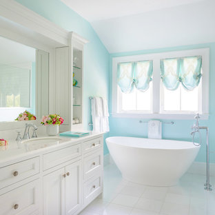 Large elegant master white floor freestanding bathtub photo in Boston with shaker cabinets, white cabinets, blue walls and an undermount sink