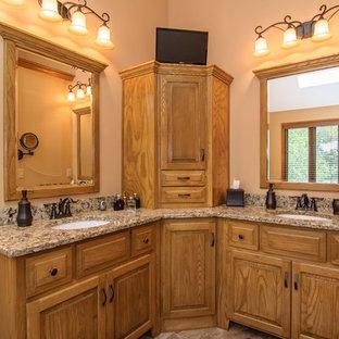 カンザスシティの中サイズのトラディショナルスタイルのおしゃれなマスターバスルーム (レイズドパネル扉のキャビネット、淡色木目調キャビネット、ドロップイン型浴槽、コーナー設置型シャワー、一体型トイレ、ベージュのタイル、セラミックタイル、ベージュの壁、セラミックタイルの床、御影石の洗面台、ベージュの床、開き戸のシャワー、アンダーカウンター洗面器) の写真