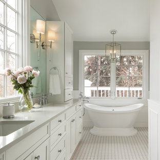Elegant mosaic tile floor and white floor freestanding bathtub photo in Denver with recessed-panel cabinets, white cabinets, gray walls, an undermount sink and gray countertops