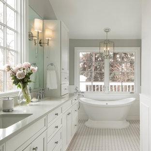 Foto de cuarto de baño tradicional con armarios con paneles empotrados, puertas de armario blancas, bañera exenta, paredes grises, suelo con mosaicos de baldosas, lavabo bajoencimera, suelo blanco y encimeras grises
