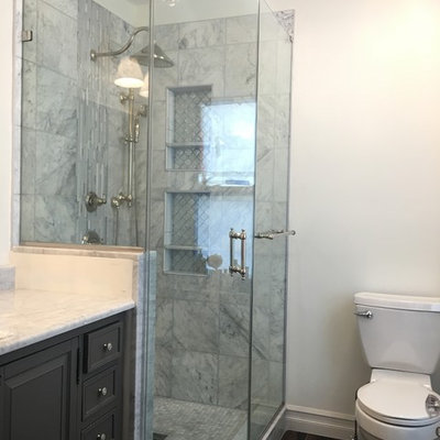 Inspiration for a mid-sized timeless master gray tile, white tile and porcelain tile dark wood floor alcove shower remodel in Newark with recessed-panel cabinets, gray cabinets, a one-piece toilet, white walls and marble countertops