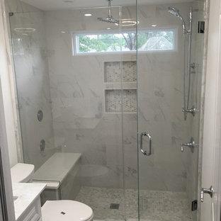 Modelo de cuarto de baño con ducha, tradicional, de tamaño medio, con armarios con paneles con relieve, puertas de armario blancas, ducha empotrada, sanitario de una pieza, baldosas y/o azulejos grises, baldosas y/o azulejos blancos, baldosas y/o azulejos de porcelana, paredes blancas, suelo con mosaicos de baldosas, lavabo bajoencimera y encimera de mármol