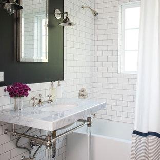 Cette image montre une salle de bain principale traditionnelle avec un plan de toilette en marbre, un carrelage métro, un combiné douche/baignoire, un plan vasque, un sol en carrelage de terre cuite, une baignoire en alcôve, un mur noir et un carrelage noir et blanc.