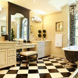 Ispirazione per una stanza da bagno padronale classica con consolle stile comò, ante con finitura invecchiata e vasca con piedi a zampa di leone
