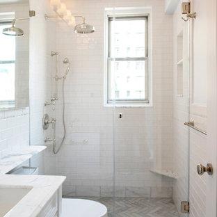 ニューヨークの小さいトラディショナルスタイルのおしゃれなマスターバスルーム (レイズドパネル扉のキャビネット、白いキャビネット、アルコーブ型シャワー、一体型トイレ、白いタイル、石タイル、白い壁、大理石の床、オーバーカウンターシンク、珪岩の洗面台) の写真