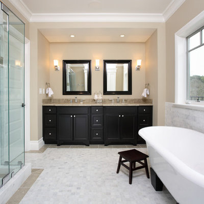 Example of a classic freestanding bathtub design in San Francisco with black cabinets