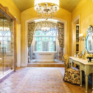 Esempio di un'ampia stanza da bagno padronale classica con consolle stile comò, ante in legno chiaro, piastrelle beige, pareti gialle, pavimento in gres porcellanato, top in marmo, vasca freestanding, doccia alcova e porta doccia a battente