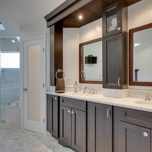 Modelo de cuarto de baño principal, tradicional, grande, con lavabo bajoencimera, armarios con paneles empotrados, puertas de armario de madera en tonos medios, encimera de ónix, bañera con patas, ducha empotrada y baldosas y/o azulejos grises