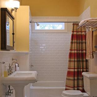 Foto di una stanza da bagno chic con lavabo a colonna, pareti gialle, vasca ad alcova, vasca/doccia, piastrelle bianche, piastrelle diamantate e pavimento multicolore