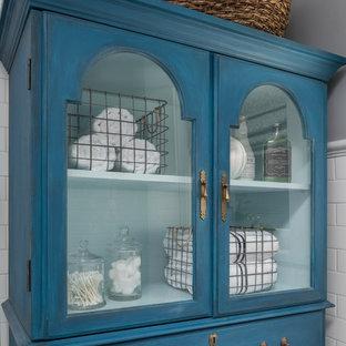 Ejemplo de cuarto de baño tradicional, pequeño, con armarios tipo vitrina, puertas de armario azules, ducha a ras de suelo, sanitario de dos piezas, baldosas y/o azulejos blancos, baldosas y/o azulejos de cerámica, paredes grises, suelo de mármol, lavabo con pedestal, suelo gris y ducha con puerta corredera