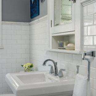 Inredning av ett klassiskt litet badrum, med luckor med glaspanel, blå skåp, en kantlös dusch, en toalettstol med separat cisternkåpa, vit kakel, keramikplattor, grå väggar, marmorgolv, ett piedestal handfat, grått golv och dusch med skjutdörr