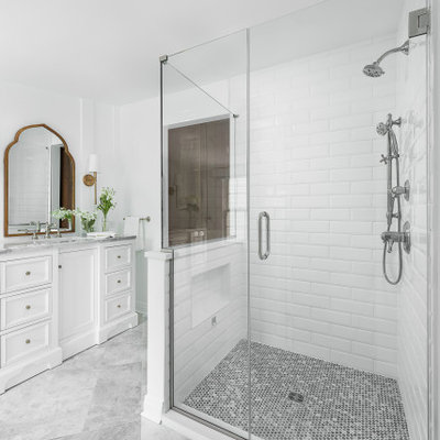 Walk-in shower - mid-sized traditional master white tile and subway tile marble floor and white floor walk-in shower idea in Chicago with recessed-panel cabinets, white cabinets, a two-piece toilet, white walls, an undermount sink, marble countertops, a hinged shower door and white countertops