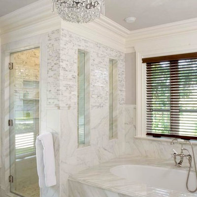 Example of a classic white tile alcove shower design in New York with an undermount tub