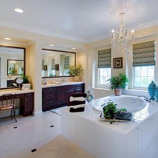 Immagine di una stanza da bagno tradizionale con ante con bugna sagomata, ante in legno bruno, top piastrellato, vasca da incasso e piastrelle bianche