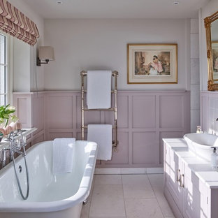 Inspiration for a medium sized traditional ensuite bathroom in Other with raised-panel cabinets, purple cabinets, a freestanding bath, pink tiles, beige walls, a vessel sink, beige floors and white worktops.