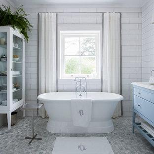 Diseño de cuarto de baño principal, clásico, con armarios con paneles empotrados, puertas de armario azules, bañera exenta, sanitario de pared, baldosas y/o azulejos grises, baldosas y/o azulejos en mosaico, paredes blancas, suelo de mármol, lavabo bajoencimera y encimera de mármol