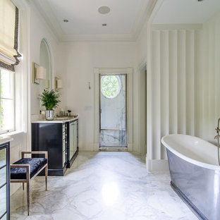 Design ideas for a traditional bathroom in Atlanta with a built-in sink, raised-panel cabinets, beige cabinets, marble worktops, a freestanding bath and beige tiles.