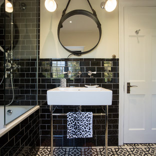 Design ideas for a small contemporary family bathroom in London with a built-in bath, a shower/bath combination, a one-piece toilet, black tiles, metro tiles, white walls, porcelain flooring and a pedestal sink.